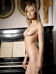 Fascinating nude coquette is posing near the black piano in one of the rooms of a famous grant museum.