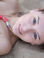 Sweet teenie strips down and shows off her nice perky tits and juicy pink twat on the sand.