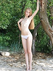 Gorgeous long haired teen beauty with a fresh slim body gracefully posing naked outdoors.