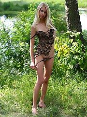Une charmante blonde se tient dans la forêt près d'un lac et ressemble à une vraie lionne en robe léopard, que l'ange prend lentement
