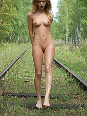 Tall blonde posing naked on the abandoned railway showing her angelic physique