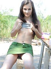 Beauté adolescente aux cheveux longs se déshabillant sur le sable pour montrer ses seins et sa délicieuse chatte.
