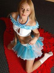 Blonde magnifique fraîche dans une jupe bleue se déshabille et montre ses jolies formes