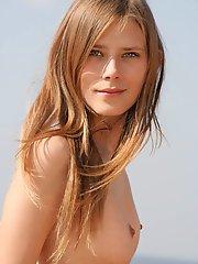 Une fabuleuse adolescente nue montre ses magnifiques bosses au bord de la mer près de vieilles ruines antiques.
