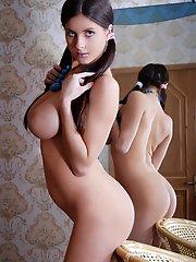 Une fille brune sexy s'amuse vraiment en posant devant le miroir.